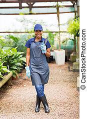 african nursery owner holding a shovel