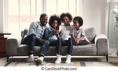 African parents and children watching video using phone on couch