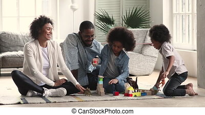 African parents and two children playing toys in living room