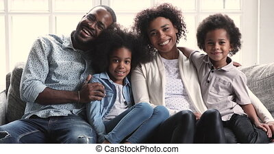 African parents posing for portrait sit with children on sofa