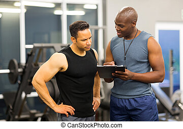 african personal trainer helping man to fill the membership form