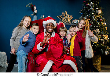 African Santa Claus and happy little children on the background of the Christmas tree