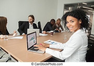 African smiling businesswoman looking at camera using laptop at