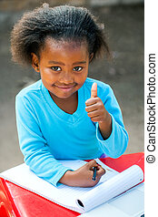 African student doing thumbs up at table. - Portrait of ...
