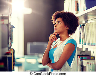 african student girl choosing book at library