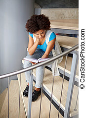 african student girl reading book on stairs