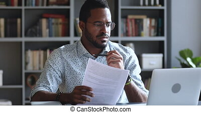 Serious focused african mixed race businessman student professional using laptop holding papers working sit at home office desk studying online doing research project preparing course work assignment