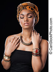 African style. Beautiful African woman wearing a headscarf and keeping eyes closed while standing against black background