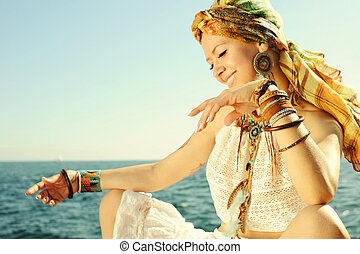 African style fashion woman, dressed in headband, white lace tank top, necklace and earrings, many leather wristbands