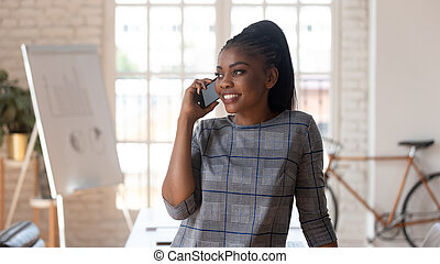 African successful businesswoman talking on phone at workplace