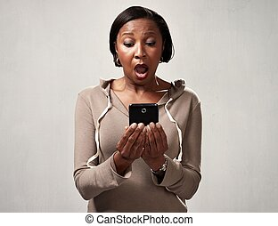 African surprised woman with smartphone