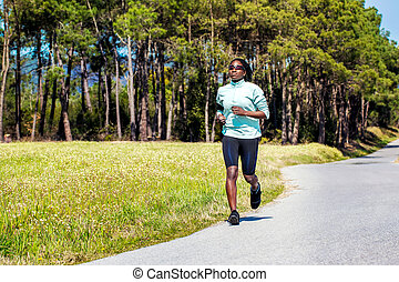 African teen girl running in countryside.