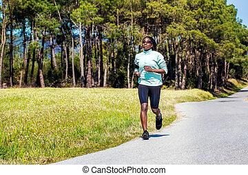 African teen girl running in countryside.