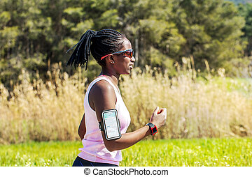 African teen running with fitness activity tracker.