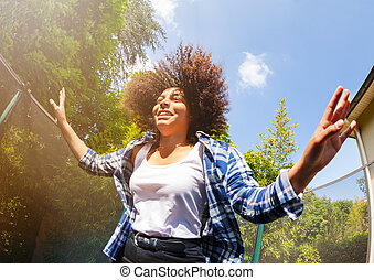 African teenage girl bouncing on the trampoline