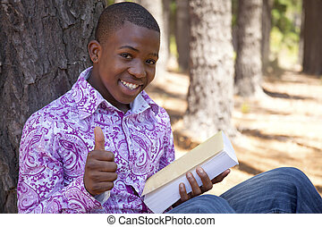 African  teenager boy reading a book outdoors