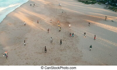 African Teenagers Playing Soccer on Beach
