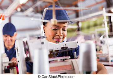 african textile worker sewing