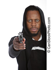 African thug aiming a gun at the camera in a threatening gesture while perpetrating a crime with focus to the gun