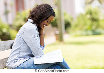 african uni student reading a book