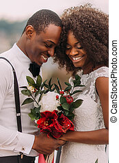African wedding couple softly smiling with eyes closed with bouquet in hands