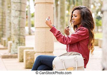 african woman applying lip gloss - beautiful african woman...