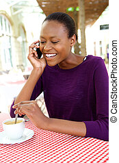 African woman at cafe having coffee and talking on mobile phone