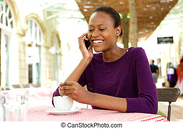 African woman at coffee shop talking on mobile phone
