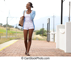 African woman at railway station making a phone call