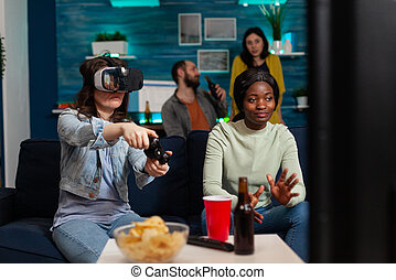 African woman cheering for friends during video game competiton wearing virtual reality goggles sitting on sofa having fun, using wireless controller. Mixed race group of people socialising.