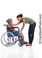african woman comforting disabled senior grandmother