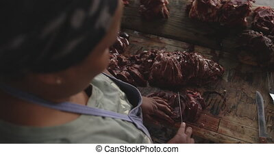 African woman cutting the meat