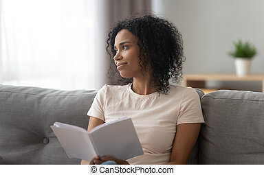 African woman sitting on couch at home distracted from reading a book, looks out the window enjoys view, delight of free time carefree moment of life, good habit get knowledge from literature concept