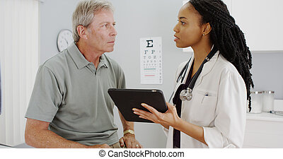 African woman doctor talking with senior patient in the office