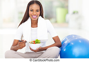 african woman eating healthy salad