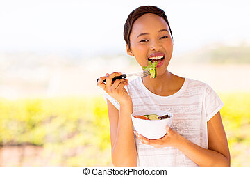 african woman eating vegetable salad