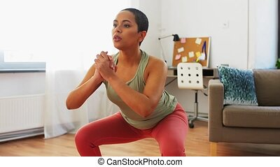 african woman exercising and doing squats at home - sport ...