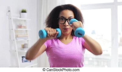 african woman exercising with dumbbells at home - fitness,...