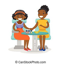 African woman getting manicure at beauty salon.