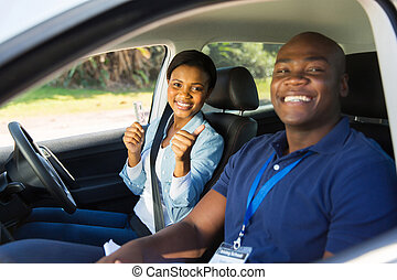 african woman has passed her driving test, holding driver's license