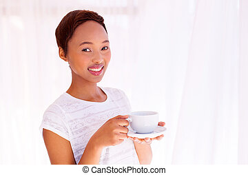 african woman having a cup of coffee