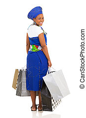 african woman holding shopping bags looking back