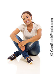 african woman in casual clothes sitting on the floor