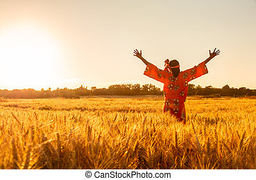 African woman in traditional clothes standing arms raised in a field of crops at sunset or sunrise