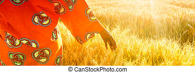 African woman in traditional clothes walking with her hand on a field of crops at sunset or sunrise