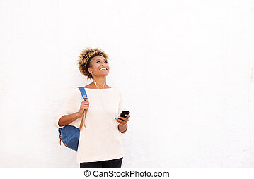 African woman listening music standing against white background