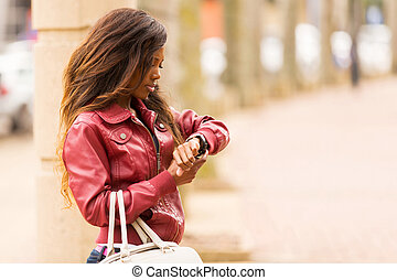 african woman looking at watch - young african woman looking...