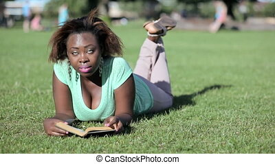 African woman lying in park reading