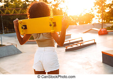 African woman outdoors with skateboard.