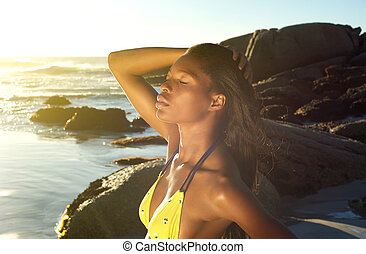 African woman posing with hand in hair at the beach